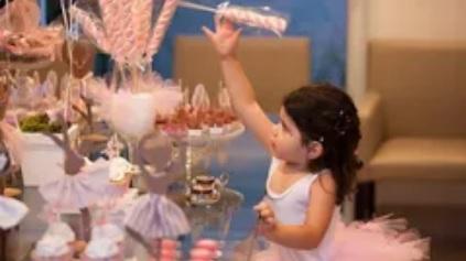 fotografia de menina vestida de bailarina e pegando um doce na mesa decorativa da festa de aniversário