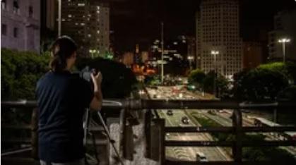 imagem de fotógrafo com câmera em ambiente noturno