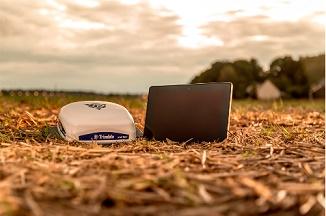 o monitor com Android e ISOBUSconectado a uma unidade de gração em um campo coberto com vegetais secos