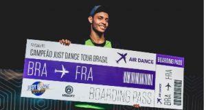 Tiago segurando o cartaz de campeão dom Just Dance Tour