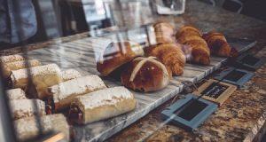 Uma mesa com pães e guloseimas de padaria