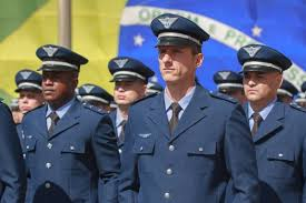 Oficiais da FAB com a bandeira do Brasil ao fundo