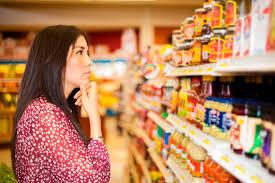 Mulher escolhendo produtos em uma gôndola de supermercado