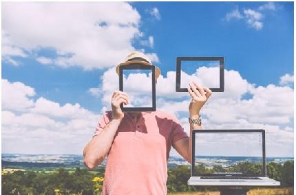 Pessoa segurando smartphone e tablet e um notebook com imagem de nuvem de internet