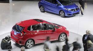 pessoas olhando 2 carros da Honda