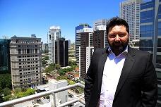 Paulo Chabbouh na sacada de um edifício entre vários ao fundo