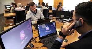 Pessoas em call center trabalhando com telefonia IP em vários computadores