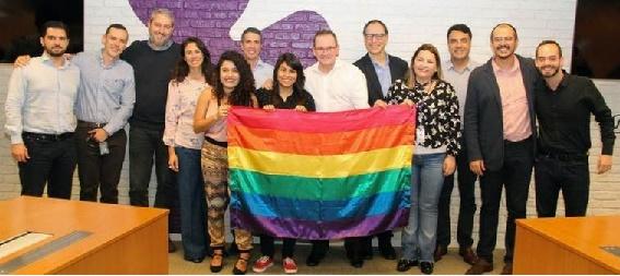 Pessoas com bandeira LGBT a vivo apoiando a causa