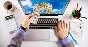 Mãos pegando dinheiro da tela de um notebook renda online