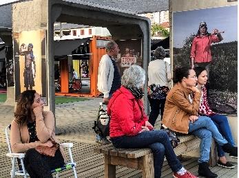 Pessoas sentadas em ponto de, ônibus olhando um painel ( povo )