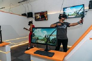 1 rapaz e 1 moça em pé jogando no ambiente de jogos