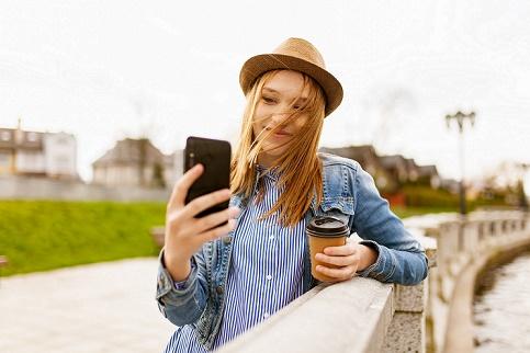 Moça loira de chapéu fazendo Selfies