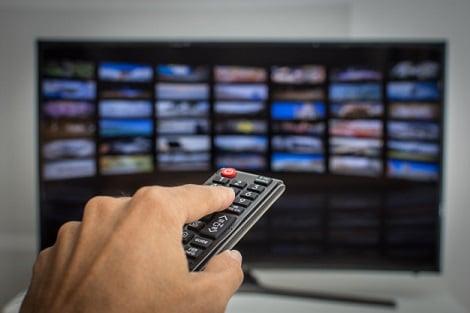 Mão com controle remoto sintonizando Streaming